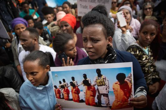 African asylum seekers and human rights activists protest against deportation in front of the Rwandan Embassy in Herzliya, on February 7, 2018. (Miriam Alster/Flash90)