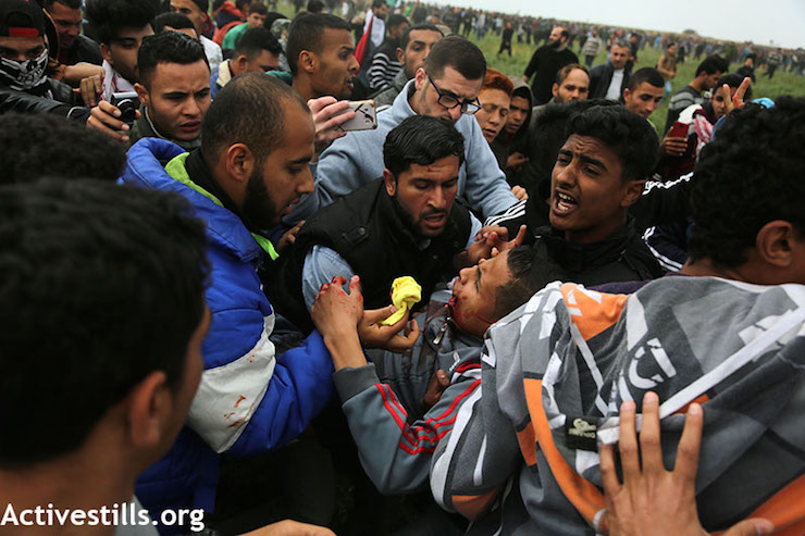 Palestinian men tend to a wounded protester during the Great Return March in Gaza, east of Jabaliya. March 30, 2018. (Mohammed Zaanoun / Activestills.org)