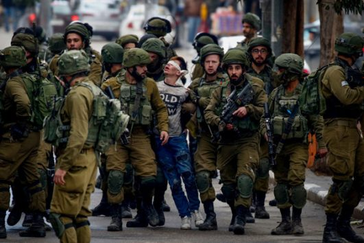 Israeli soldiers arrest a Palestinian boy during a protest in the West Bank city of Hebron, following US President Donald Trump's recognition of Jerusalem as the capital of Israel, on December 7, 2017. (Wisam Hashlamoun/Flash90)