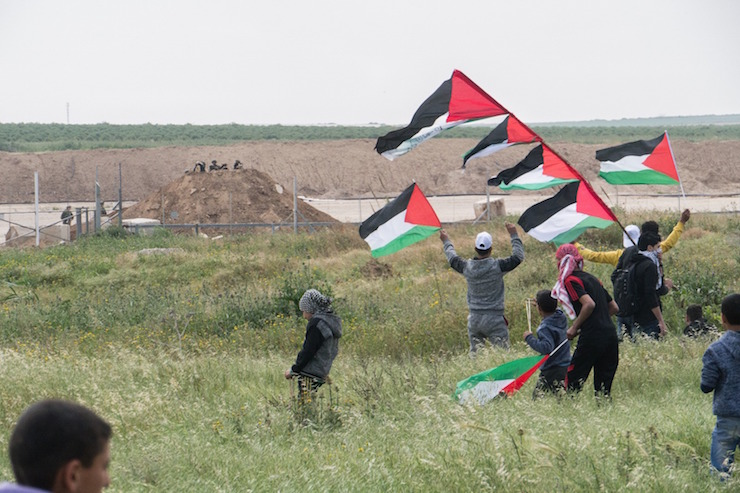 Palestinian youth approach the border fence as Israeli snipers look on from a mound of dirt on the other side, east of Shajaia, Gaza, during the start of the 'Great Return March.' March 30, 2017. (+972 Magazine)
