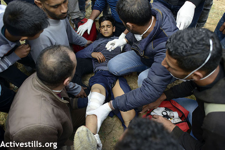 Palestinians tend to a boy who was shot in the leg by Israeli snipers during the Great Return March in Gaza, east of the Jabaliya refugee camp. March 30, 2018. (Mohammed Zaanoun / Activestills.org)