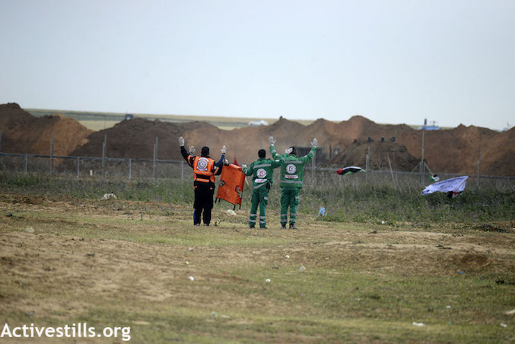 Palestinian medics signal to Israeli soldiers that they are unarmed as they attempt to retrieve wounded protesters east of Jabaliya during the Gaza return march, seen from the Palestinian side. March 30, 2018. (Mohammed Zaanoun / Activestills.org)