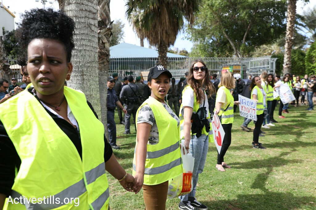 Asylum seekers and residents of south Tel Aviv serve as ushers during a women's march through the city to demonstrate against the planned deportation of thousands of asylum seekers from Israel, March 9, 2018. (Oren Ziv/Activestills.org)