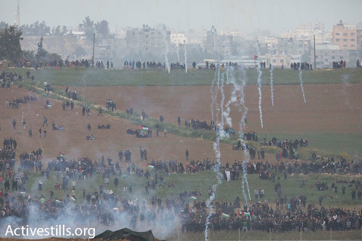 Israeli forces fire tear gas and live ammunition at Palestinian protesters near the Gaza border fence during the start of the Great Return March, seen from the Israeli side of the border. March 30, 2018. (Oren Ziv / Activestills.org)