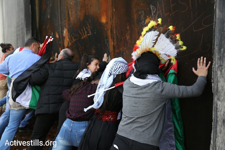 Demonstrators attempt to open a gate that is part of the separation wall in Bil'in. March 2, 2018. (Activestills.org)