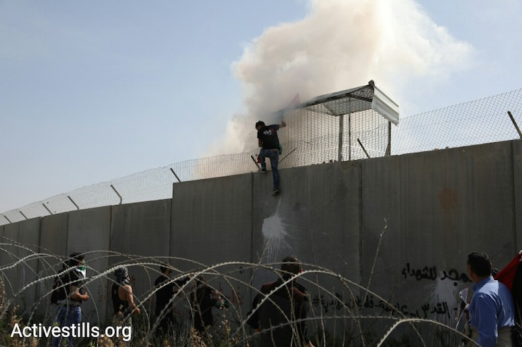 A demonstrator tries to scale the separation barrier in Bil'in. March 2, 2018. (Activestills.org)
