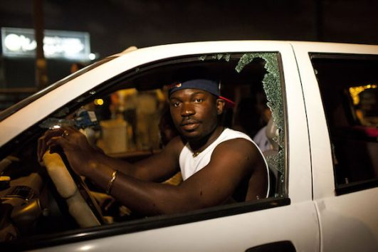 A man from the Ivory Coast drives his car after a mob smashed its windows following a protest against African refugees and asylum seekers in Tel Aviv's Hatikva neighborhood on May 23, 2012. (Oren Ziv/Activestills.org)