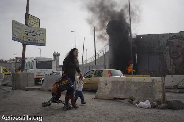 A Palestinian mother and her child walk past the Israeli army's Qalandiya checkpoint as clashes take place. (File photo by Oren Ziv/Activestills.org)