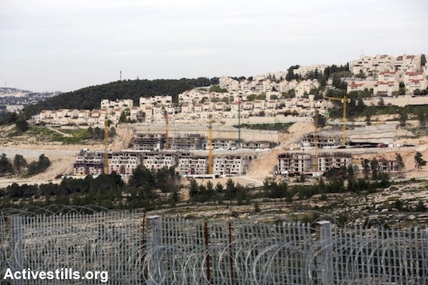 A new portion of the Separation Wall, made by a high barbed wire fence in the West Bank village of Walajeh, with at the background the growing settlement of Gilo, March 18, 2018. (Anne Paq/Activetsills.org)