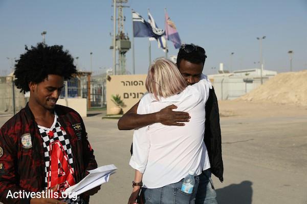 Asylum seekers and an Israeli activist outside of Saharonim after Israel released 207 asylum seekers imprisoned for refusing deportation. April 15, 2018. (Oren Ziv / Activestills.org)