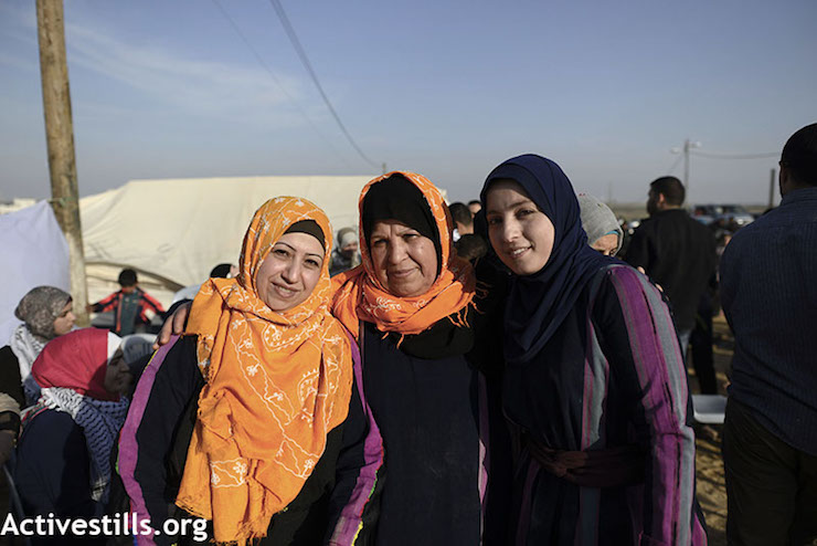 Um Youssef Lubbad, middle, poses at the protest encampment in Gaza, east of Shajaiya. (Mohammed Zaanoun / Activestills.org)