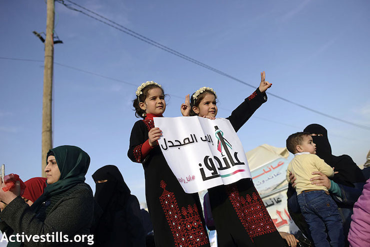 "Palestinian girls hold a sign that says ""We'll return to Al Majdal."" (Mohammed Zaanoun / Activestills.org)"