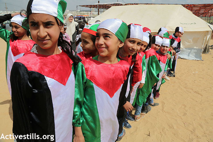 Palestinian children dressed in the colors of the Palestinian flag, at the protest encampment in Gaza east of Shujaiya. (Mohammed Zaanoun / Activestills.org)