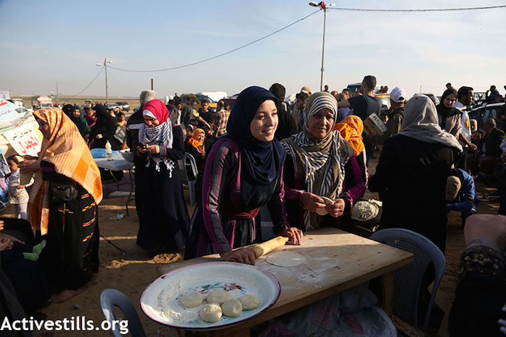 Palestinian women roll dough at the protest camp in Gaza, east of Shujaiya. April 11, 2018. (Mohammed Zaanoun / Activestills.org)
