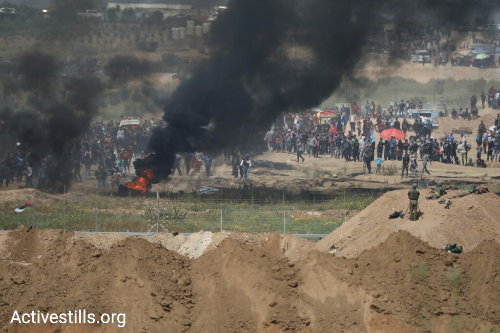 Palestinian protesters burn tires at the Gaza-Israel border during the eighth day of the 'Great Return March,' Shuja'iyya, Gaza City, April 6, 2018. (Oren Ziv/Activestills.org)
