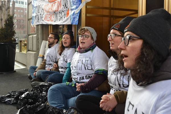 Young Jewish activists from IfNotNow link arms outside the Israeli Consulate of New England in Boston. The activists read the Mourner's Kaddish and demanded the consul general condemn IDF violence against Palestinian marchers in Gaza, April 3, 2018. (Schyler Cunningham)