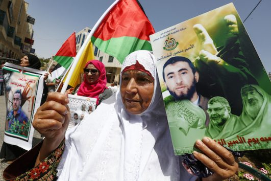 Palestinians hold photos of Palestinian prisoners during a protest to demand the release of their relatives jailed in Israeli prisons, on the Prisoners' Day in the West Bank city of Hebron, on April 17, 2018. (Wisam Hashlamoun/Flash90)