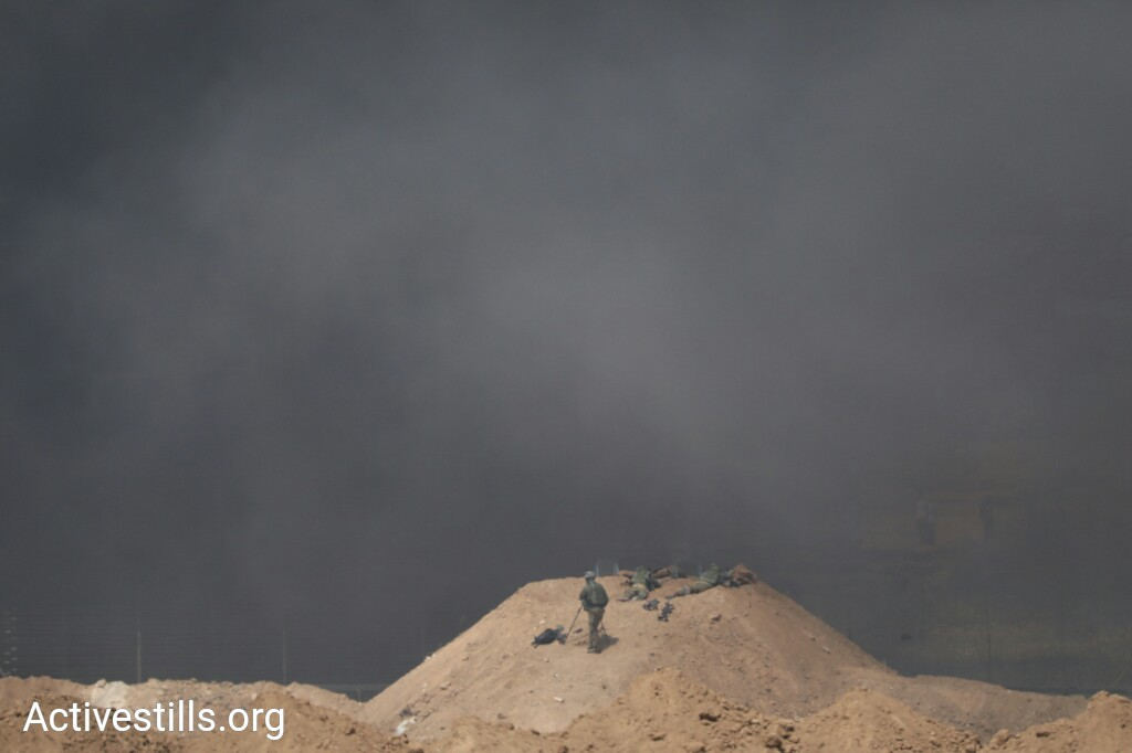 Smoke billows over the Gaza-Israel border as Palestinian protesters burn tires during the eighth day of the 'Great Return March,' Shuja'iyya, Gaza City, April 6, 2018. (Oren Ziv/Activestills.org)