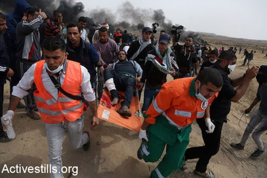 Palestinian medics evacuate a protester wounded during the Great Return March in Gaza. April 20, 2018. (Mohammed Zaanoun / Activestills.)