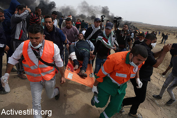 Palestinian medics evacuate a protester injured during the Great Return March in Gaza. April 20, 2018. (Mohammed Zaanoun / Activestills.)