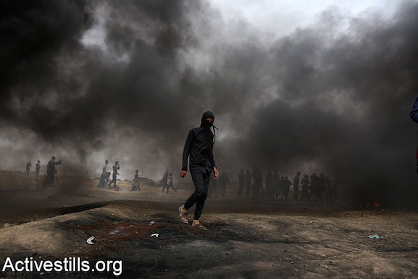 A Palestinian protester walks through the smoke of burning tires during the Great Return March demonstrations. April 20, 2018. (Mohammed Zaanoun / Activestills.org)