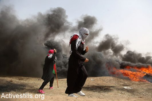 Palestinian women walk between burning tires during the Great Return March protests in Gaza. April 20, 2018. (Mohammed Zaanoun / Activestills.org)
