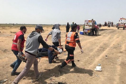 Medics carry a a protester wounded during the Gaza return march demonstrations. April 13, 2018. (Mohammed Sabah/B'Tselem)