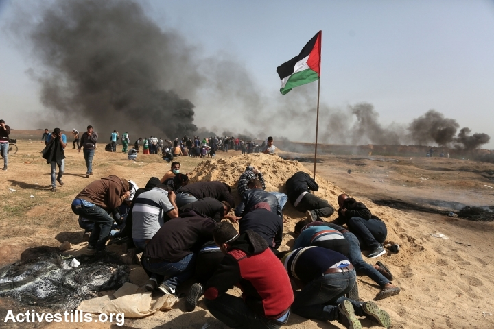 Palestinian protesters take cover behind a dirt mound as Israeli soldiers open fire from across the border in the distance, east of Jabaliya, Gaza Strip, April 6, 2018. Israeli snipers have killed over 30 people and shot over 1,000 others since The Great Return March began a week earlier. (Mohammed Zaanoun/Activestills.org)