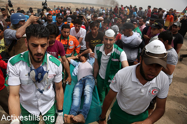 Palestinian medics carry a demonstrator on a stretcher during the Great March of Return protests, May 4, 2018. (Mohammed Zaanoun/Activestills.org)