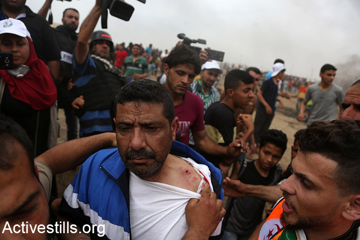 A Palestinian demonstrator is wounded in his shoulder during the Great March of Return protests on the Gaza-Israel border, May 4, 2018. (Palestinian medics carry a demonstrator on a stretcher during the Great March of Return protests, May 4, 2018. (Mohammed Zaanoun/Activestills.org)