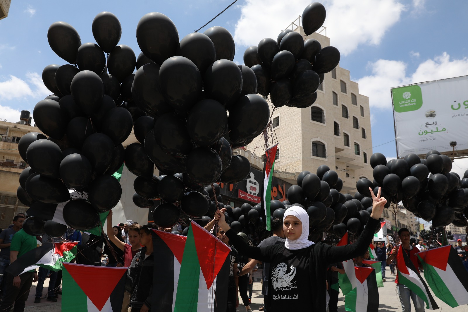 Palestinians in Qalandiya checkpoint fly Palestinian flags attached to balloons, in solidarity with Gaza and against the opening of the new U.S. embassy in Jerusalem, May 14, 2018. (Oren Ziv/Activestills.org)