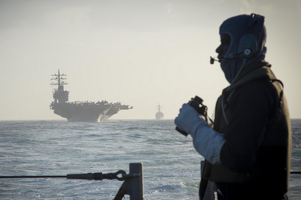 An American sailor stands lookout aboard a guided missile cruiser with the USS Eisenhower aircraft carrier seen in the background. (U.S. Navy photo/William Jenkins)