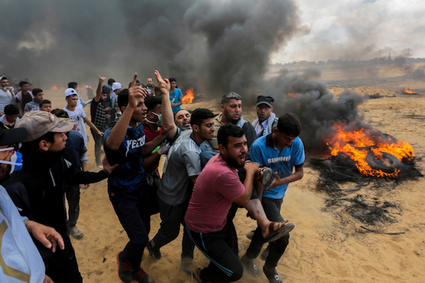 Protesters carry away someone who was shot by an Israeli sniper along the Gaza border, May 14, 2018. (Abed Rahim Khatib/Flash90)
