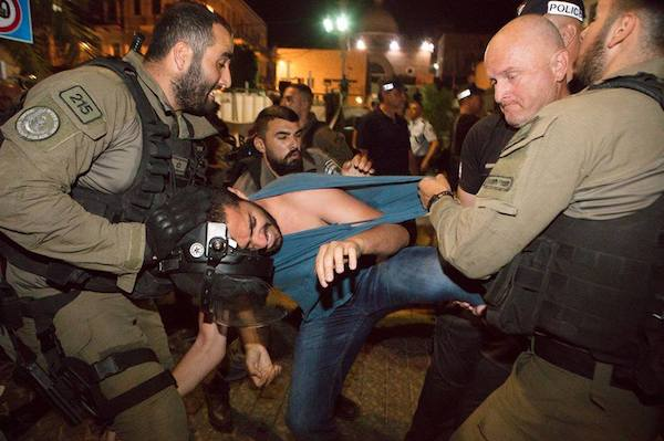 Israeli riot police arrest a protester in downtown Haifa during a demonstration against the mass killings in Gaza, May 19, 2018. (Nadine Nashef)