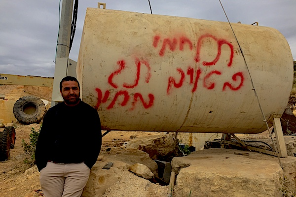 Mahmoud, who works in Urif's quarry, stands next to a container that was graffitied by settler youth during a recent spate of hate crimes in the village. The graffiti reads: 'Fight your enemy. Price tag.' (Edo Konrad)