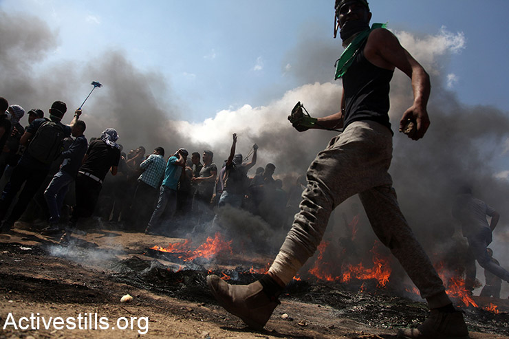 A Palestinian man holds stones as he walks by burning tires at a protest inside the Gaza Strip, May 14, 2018. (Mohammed Zaanoun/Activestills.org)