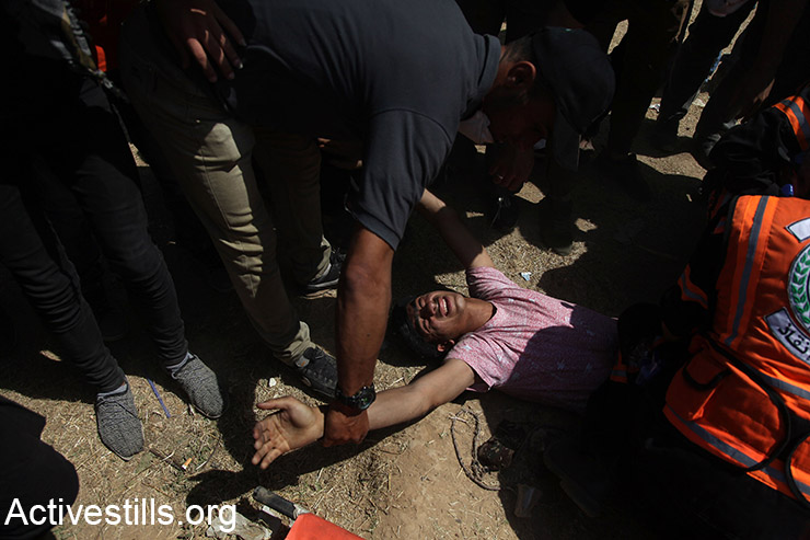 Medics help a wounded Palestinian during demonstrations on the Gaza border, May 14, 2018. (Mohammed Zaanoun/Activestills.org)