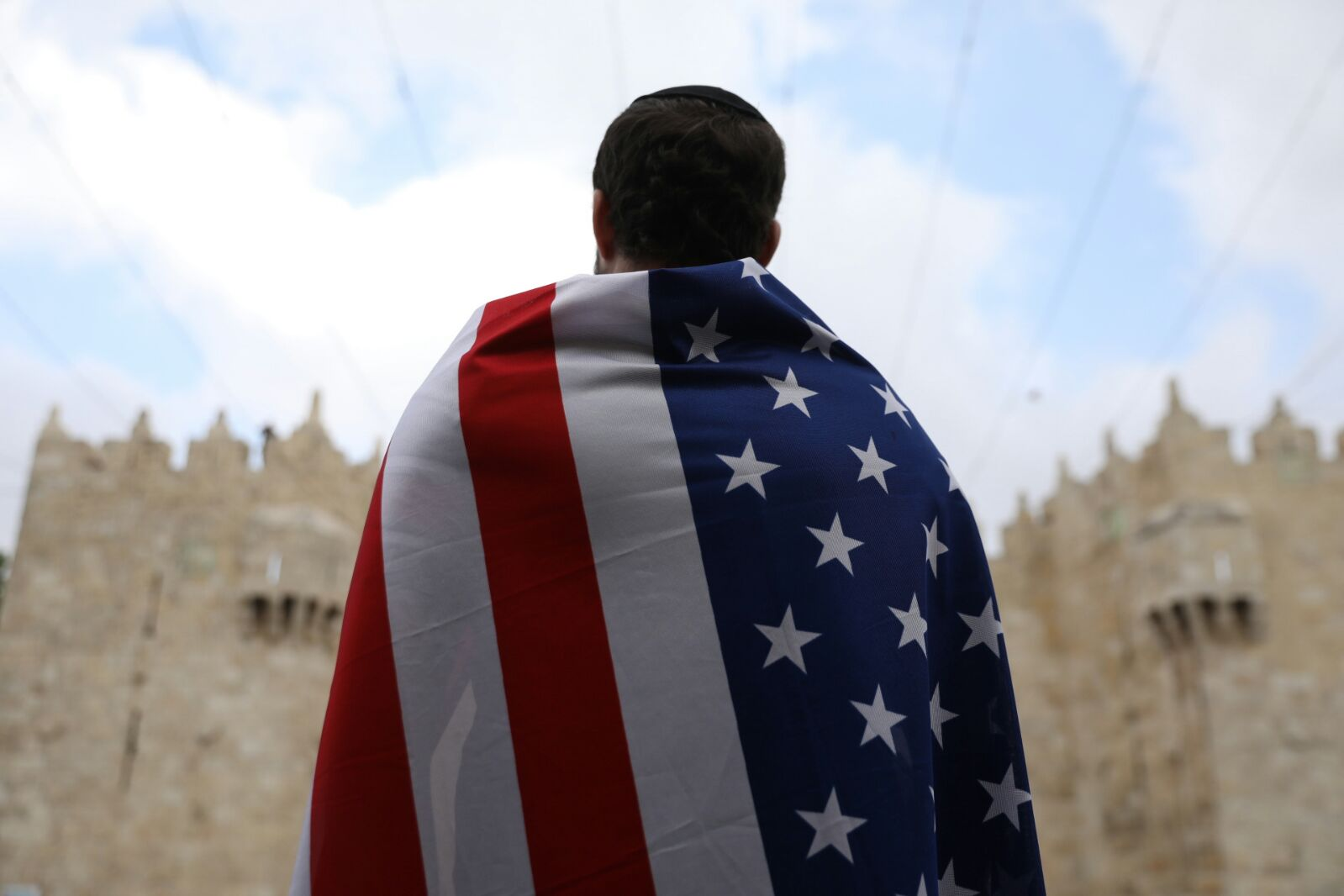 A man draped in an American flag stands in front of Damascus Gate during the annual 'March of the Flags,' as part of Jerusalem Day, May 13, 2018. (Oren Ziv/Activestills.org)