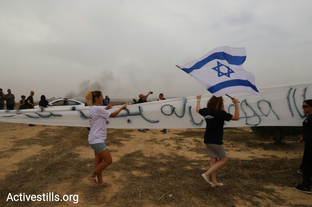 Supporters of Defense Minister Avigdor Liberman hold up a giant banner reading: 'Only Liberman understands Arabic — don't mess with him' near the Israel-Gaza border, May 4, 2018. (Oren Ziv/Activestills.org)