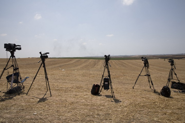 Cameras belonging to news crews stationed at the Israeli side of the border with Gaza attempt to capture the clashes near the fence, May 15, 2018. (Oren Ziv/Activestills.org)