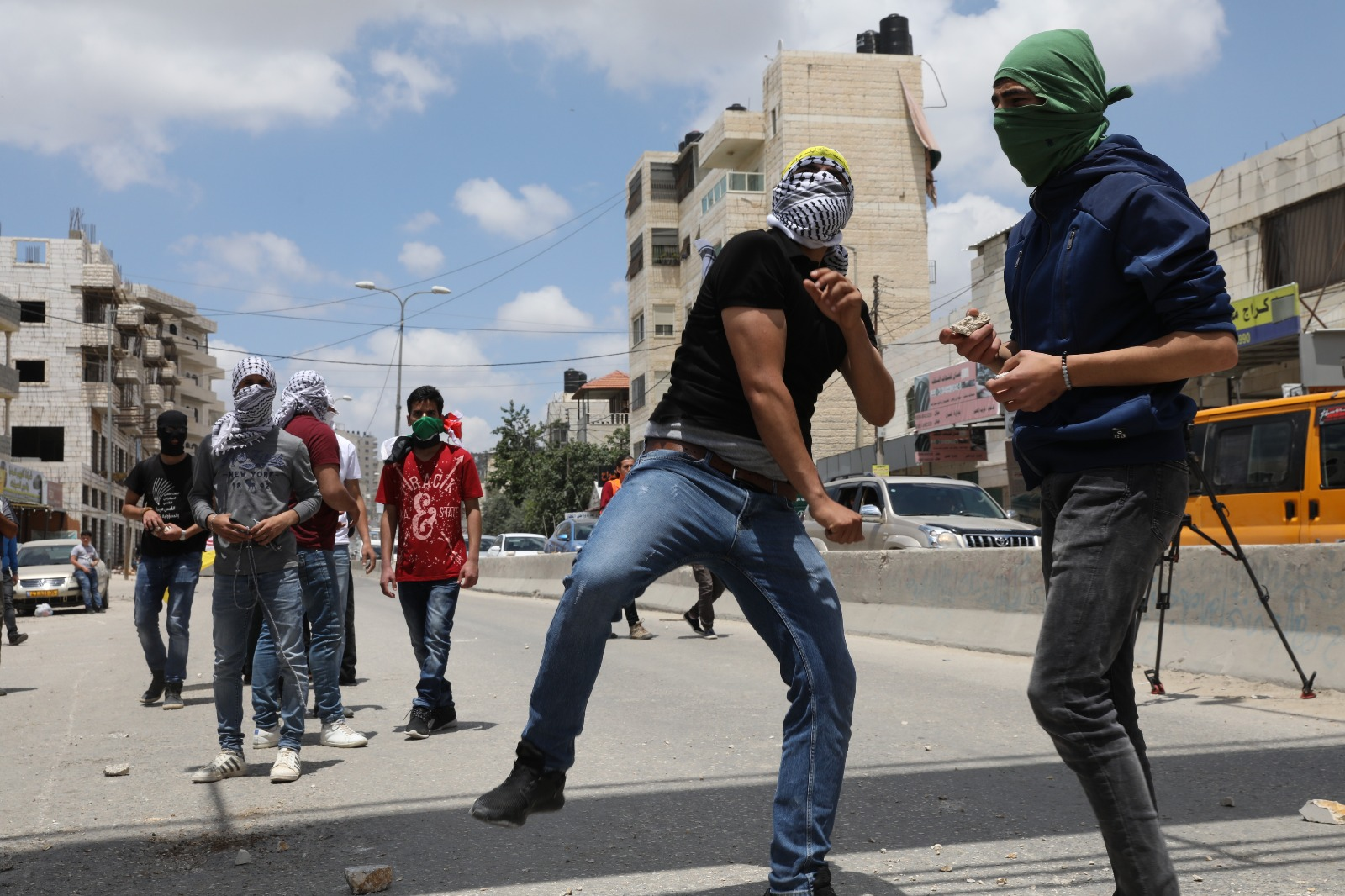 Palestinians throw stones at Israeli soldiers during clashes at Qalandiya checkpoint, near Jerusalem, May 14, 2018. (Oren Ziv/Activestills.org)