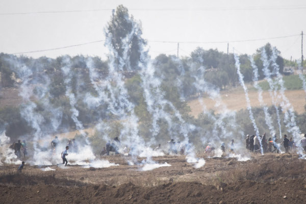 Gaza protesters run from tear gas and live ammunition during Friday's Great Return March demonstrations. May 11, 2018. (Oren Ziv / Activestills.org)