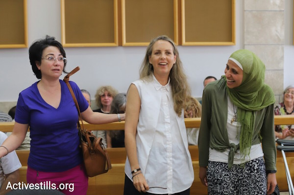 MK Hanin Zoabi, attorney Gaby Lasky, and Dareen Tatour stand at the start of Tatour's sentencing hearing. May 3, 2018. (Oren Ziv / Activestills.org)