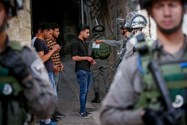 Israeli soldiers check the ID's of Palestinian boys in the Old City of Hebron, West Bank, May 23, 2018. (Wisam Hashlamoun/Flash90)