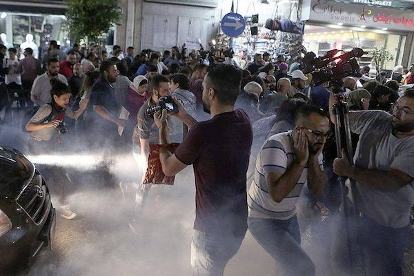 Palestinian protesters flee from tear gas fired by Palestinian Authority's police forces during a demonstration against the PA's sanctions on Gaza, June 13, 2018. (ارفعوا العقوبات)