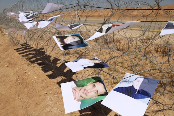 Pictures of slain Palestinian demonstrators hang on barbed wire near the Gaza-Israel separation barrier. June 26, 2018. (Oren Ziv / Activestills.org)