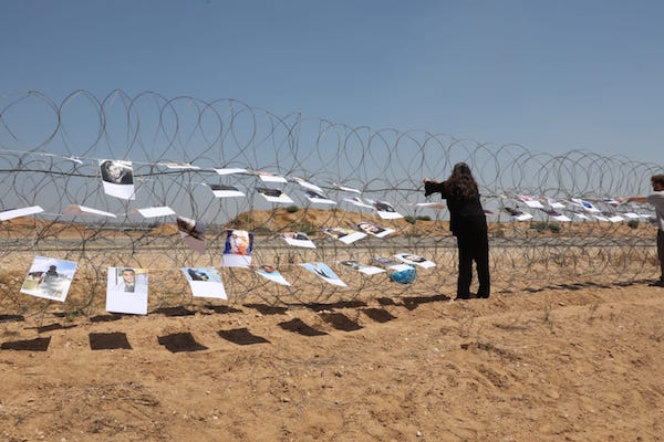 Israeli and international activists hang pictures of slain Palestinian demonstrators on a barbed-wire fence near the Gaza-Israel separation barrier. (Oren Ziv / Activestills.org)