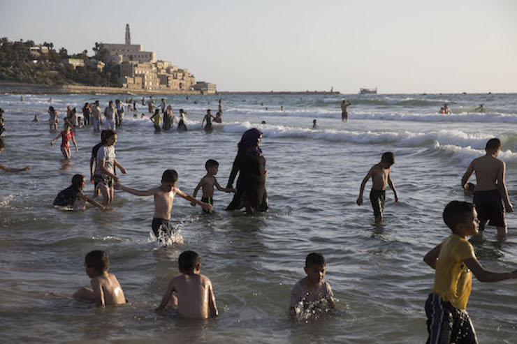 Palestinians from the West Bank swim near Jaffa during the Eid al-Fitr holiday. June 17, 2018. (Oren Ziv/Activestills.org)