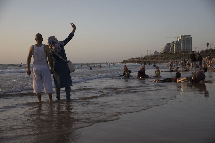 A couple takes a selfie as Palestinians from the West Bank celebrate Eid al-Fitr at the beach in Tel Aviv-Jaffa. (Oren Ziv/Activestills.org)