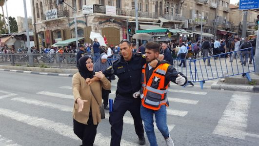 Israeli police arrest a Palestinian Red Crescent medic as a woman pleads with the officer, 'That's my son!' (Sasha Belenkiy)